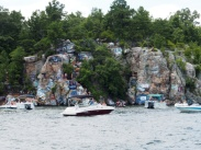 some sort of rock formation with graffiti and lots of boats. interesting